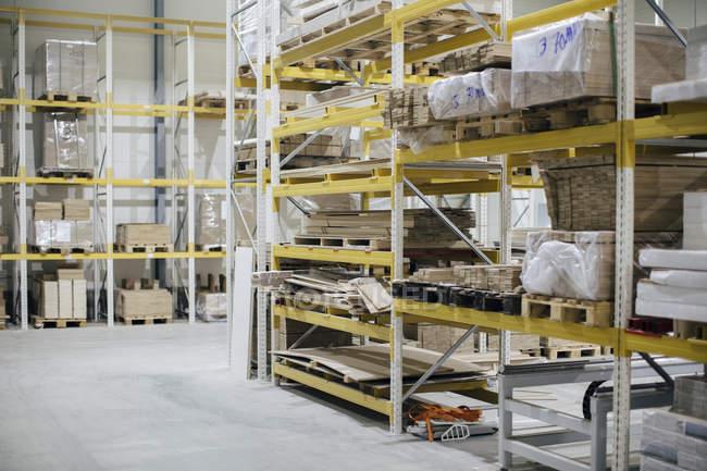 Empilement de planches de bois sur des supports dans la maison de distribution — Photo de stock