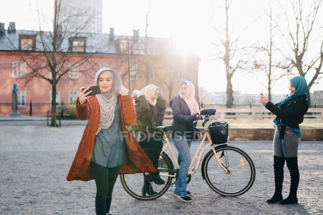 Junge Frau unter Selfie gegen weibliche Freunde mit dem Fahrrad in der Stadt — Stockfoto