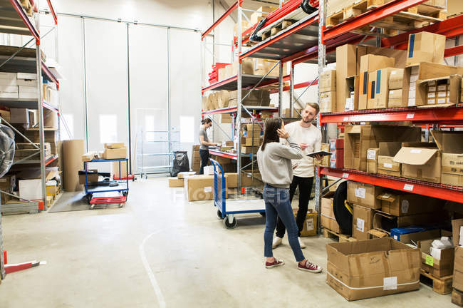 Coworkers examining while standing at warehouse — Stock Photo