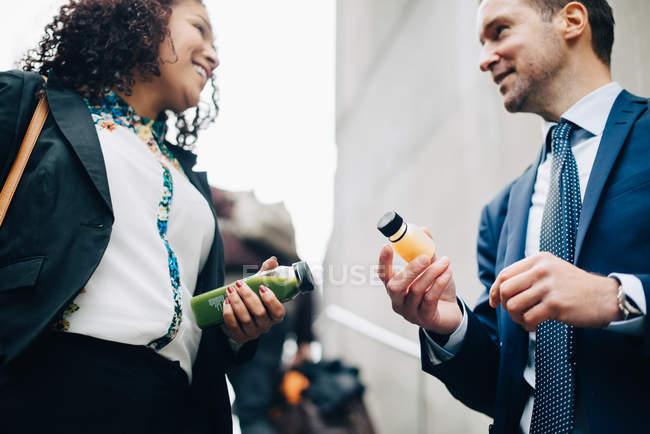 Низький кут зору посміхаючись колегами по бізнесу, стоячи з пляшок напою в місті — стокове фото