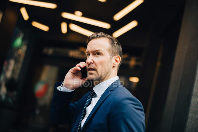 Uomo d'affari maturo che comunica sul telefono astuto mentre distogliendo in città — Foto stock