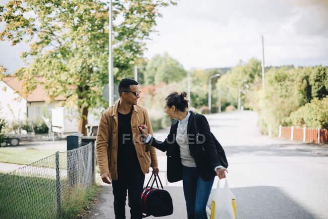 Lächelnder Mann und Frau, die sich bei sonnigem Wetter auf der Straße in der Stadt unterhalten — Stockfoto