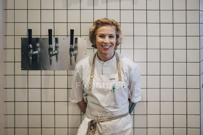 Portrait of smiling female chef standing against white tile wall in restaurant kitchen — Stock Photo