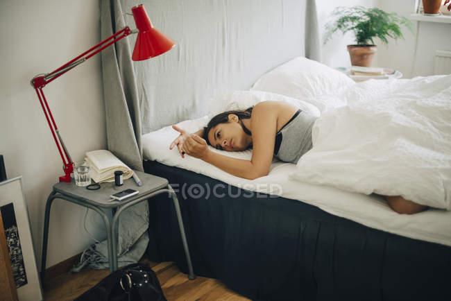 Frau kontrolliert Blutzuckerspiegel, während sie im Schlafzimmer im Bett liegt — Stockfoto