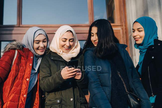 Feliz mujer musulmana amigos compartiendo teléfono inteligente de pie contra la puerta de entrada en la ciudad - foto de stock