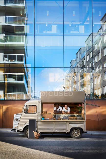 Propriétaires masculins dans un camion alimentaire garé sur la rue de la ville contre le bâtiment en verre — Photo de stock