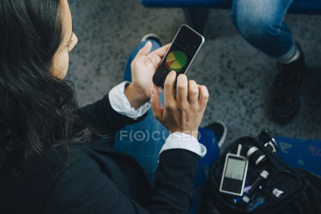 Woman checking blood sugar level and using mobile phone in train — Stock Photo