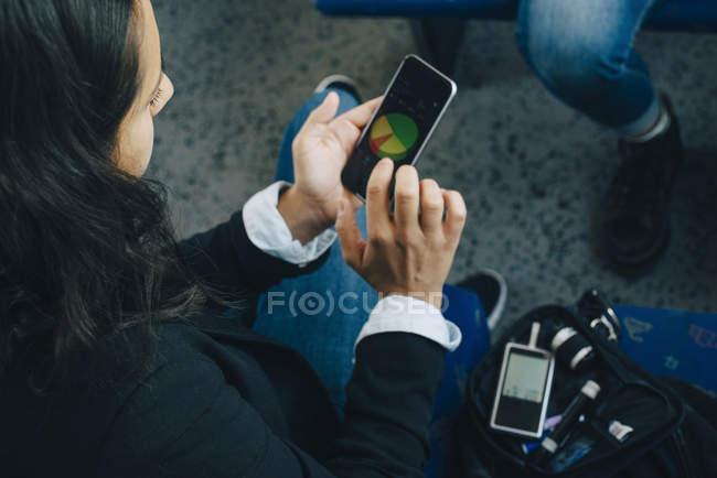 Жінка перевірки рівня цукру крові і використання мобільного телефону у поїзд — стокове фото