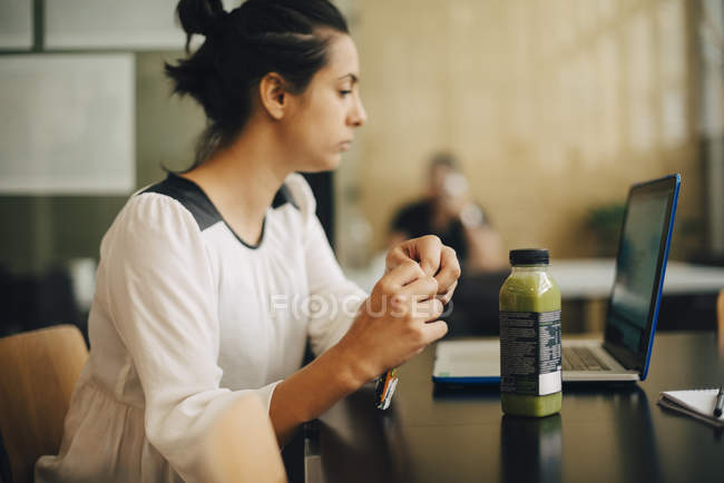 Geschäftsfrau isst Essen und trinkt gesund, während sie Laptop am Schreibtisch benutzt — Stockfoto