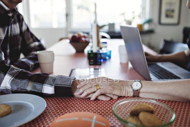 Image recadrée d'une femme âgée tenant la main d'un homme sur une table à manger à la maison — Photo de stock