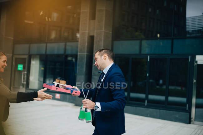 Vista laterale dell'uomo d'affari maturo che dà cibo e bevande al collega femmina mentre parla al cellulare contro costruzione — Foto stock