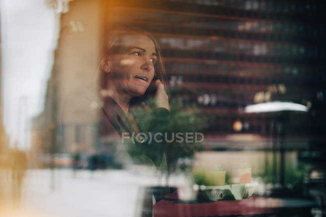 Mature businesswoman talking on mobile phone while holding food and drink in cafe seen from window — Stock Photo