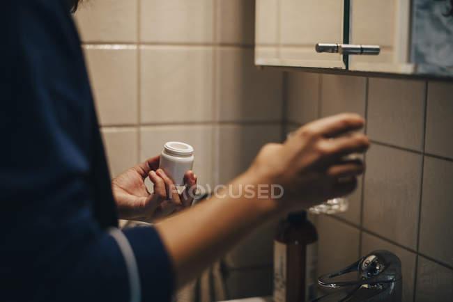 Abgeschnittenes Bild einer Frau mit Glas und Pillen im Badezimmer — Stockfoto