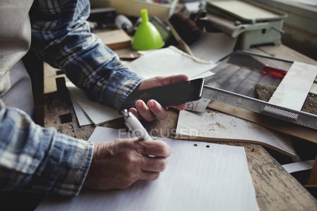 Zugeschnittenes Bild des Besitzers halten Handys beim Schreiben auf Papier an Werkbank — Stockfoto