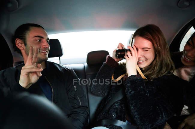 Lächeln Frau fotografiert männlichen Freund gestikulierend Friedenszeichen während der Fahrt im Taxi in der Stadt — Stockfoto
