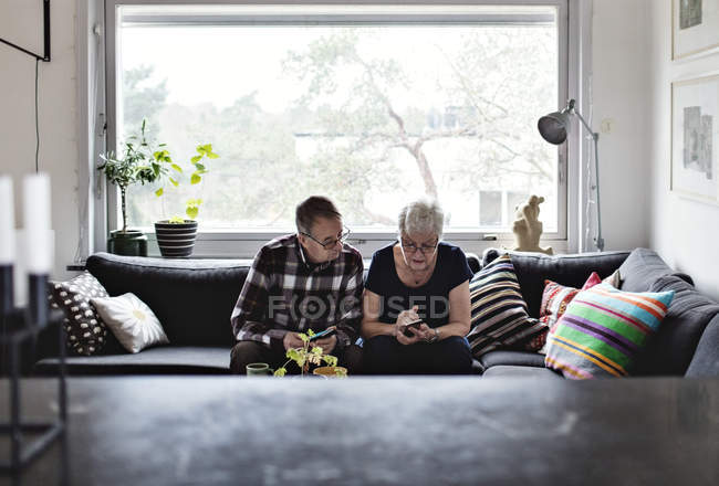 Senior couple using smart phones sitting on sofa in living room against window at home — Stock Photo