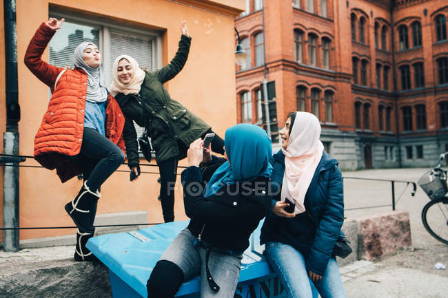 Young woman photographing cheerful female friends against building in city — Stock Photo