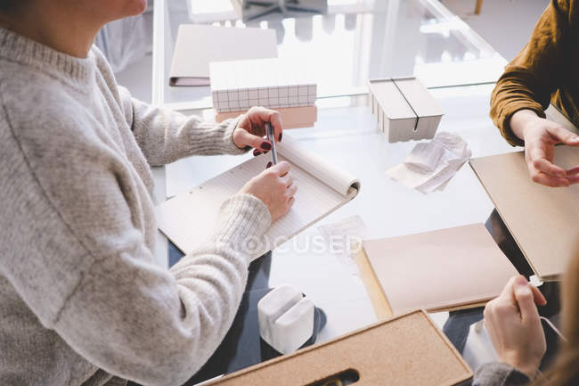 High angle view of female design professional with note pad discussing with colleagues at desk in workshop — Stock Photo