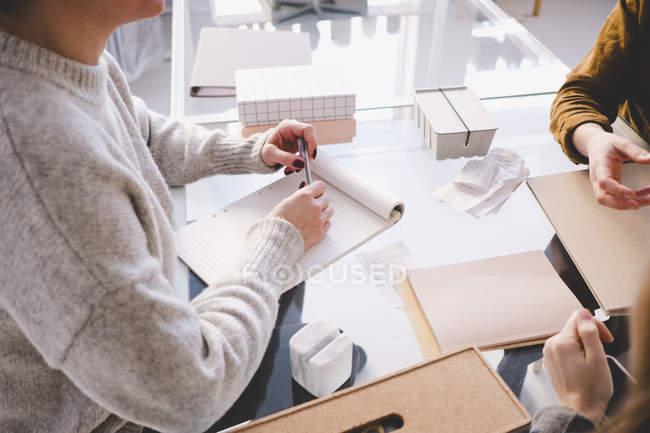 Высокий угол зрения женский дизайн профессионал с Блокнот, обсуждать с коллегами на стол в мастерской — стоковое фото