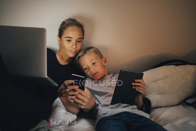 Братів і сестер лежачи на ліжку при обміні смарт-телефону в домашніх умовах — стокове фото