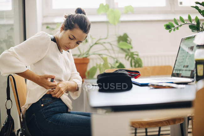 Бізнес-леді ін'єкційні інсуліну, сидячи на столі в офісі — стокове фото
