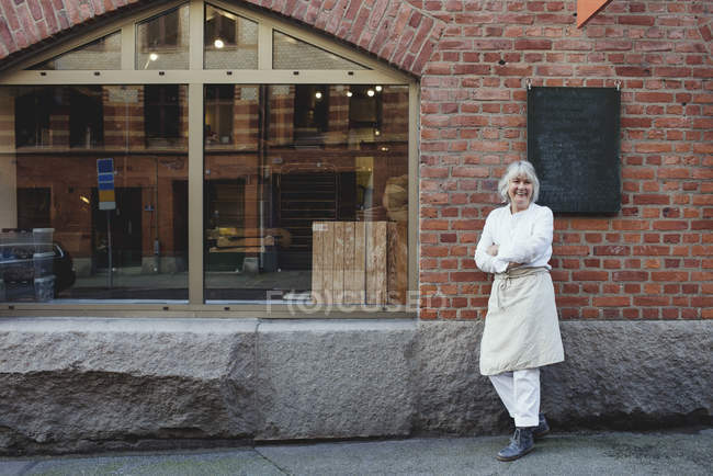 Full length of smiling baker standing on sidewalk against brick wall — стокове фото