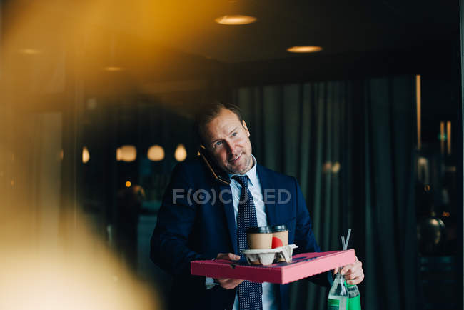 Mature businessman talking on mobile phone while carrying food and drinks in cafe — Stock Photo
