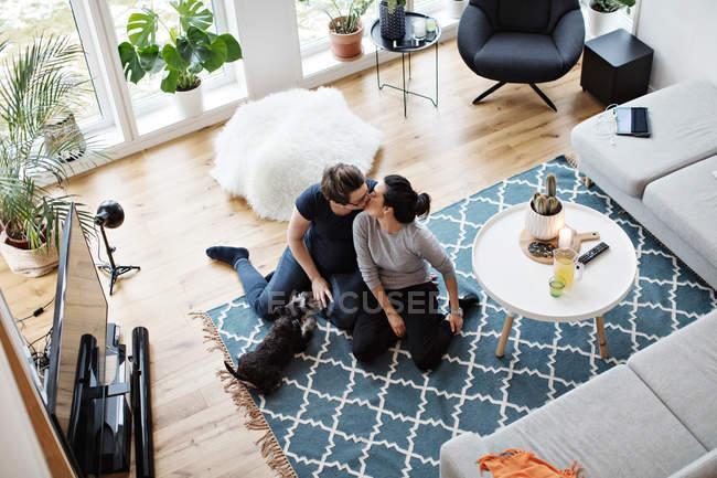 Vista ad alto angolo di coppia lesbica baciare mentre seduto da cane su tappeto in soggiorno — Foto stock
