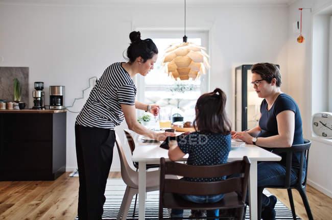 Mujer sirviendo comida a las niñas y mujeres en mesa de comedor - foto de stock