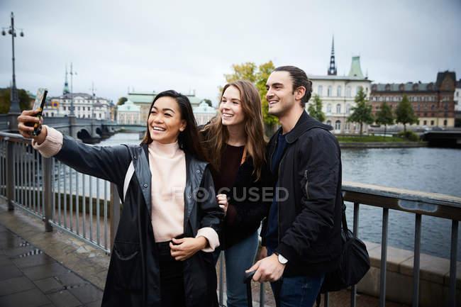 Mulher tomando selfie através de telefone móvel em pé na ponte na cidade a sorrir — Fotografia de Stock