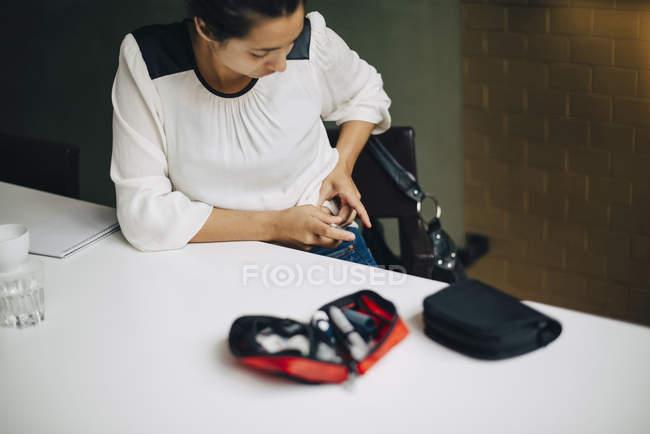 Бізнес-леді ін'єкційні інсуліну в черевній порожнині сидячи за столом — стокове фото