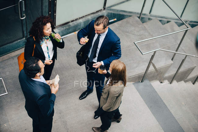 High angle view of business colleagues standing with food and drink at staircase in city — Stock Photo