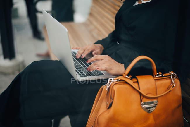 Midsection de la mujer de negocios escribiendo en el ordenador portátil sentado en el refugio de autobús visto desde el vidrio - foto de stock