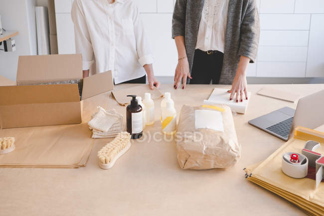 Midsection of female entrepreneurs standing with various manufacturing objects on table in workshop — Stock Photo
