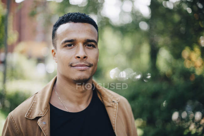 Close-up portrait of man wearing brown jacket standing by plants — Stock Photo