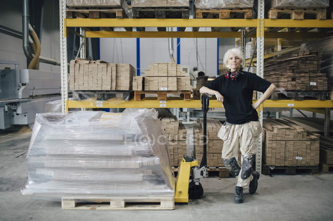 Full length of confident worker standing by stacked planks on pallet jack at industry — Stock Photo
