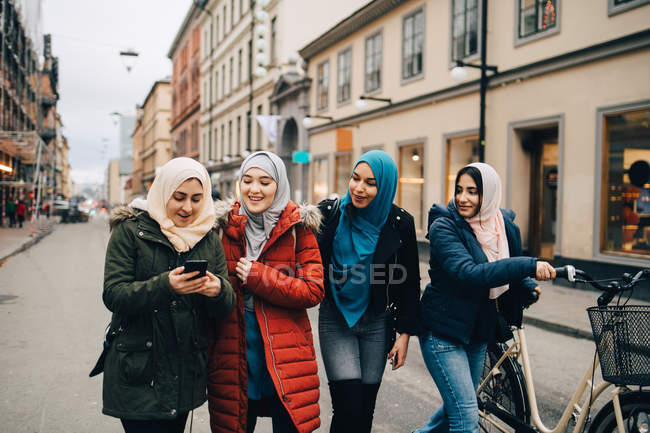 Multi-ethnic Muslim friends walking with bicycle and mobile phone on street in city — Stock Photo