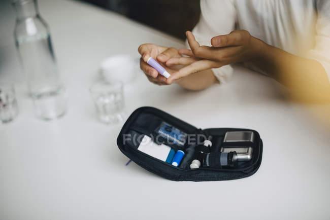 Abgeschnittenes Bild einer Geschäftsfrau bei Blutzuckertest am Tisch im Büro — Stockfoto