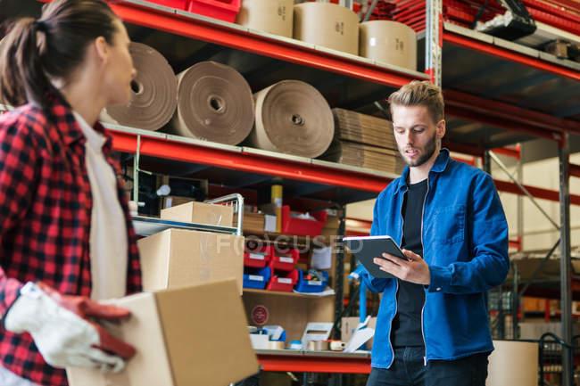 Trabajador masculino usando tableta digital mientras que la mujer tiene caja de cartón en el almacén. - foto de stock