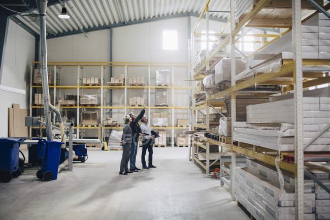 Toute la longueur des gens d'affaires qui regardent rack dans l'industrie du bois — Photo de stock