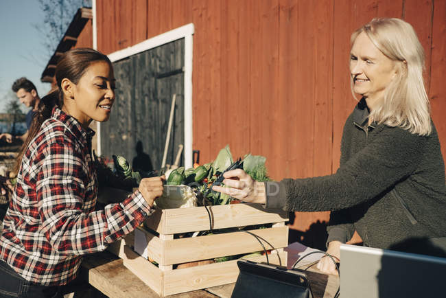 Mature woman paying female farmer through credit card at market — Stock Photo