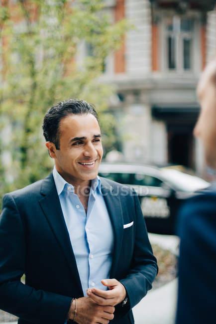 Uomo d'affari sorridente che distoglie lo sguardo mentre levandosi in piedi in città — Foto stock