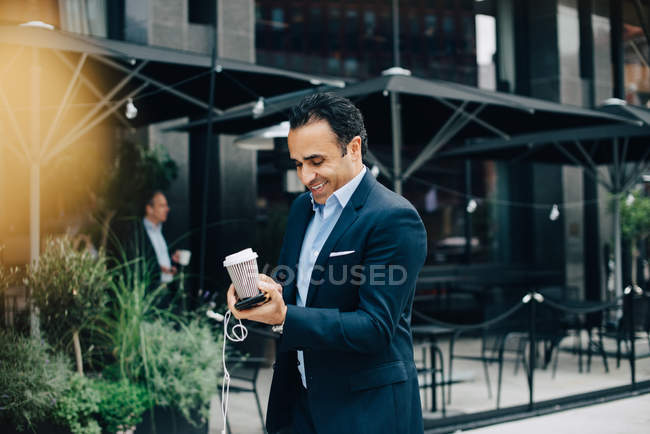 Smiling mature businessman holding disposable coffee cup with smart phone and earphones in city — Stock Photo