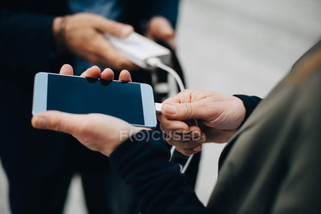 Midsection of mature businesswoman charging mobile phone while standing with coworker — Stock Photo