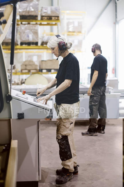 Full length of manual worker operating machine while standing by colleague at industry — Stock Photo