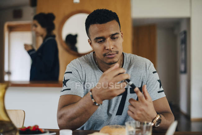 Man checking blood sugar level while having breakfast at home — Stock Photo