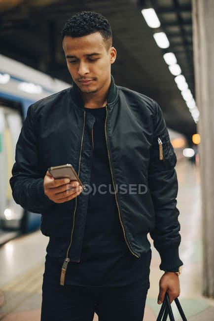 Uomo che utilizza il telefono cellulare in piedi in treno alla stazione della metropolitana — Foto stock