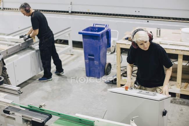 Hochwinkelaufnahme männlicher Arbeiter, die Maschinen in der Industrie bedienen — Stockfoto
