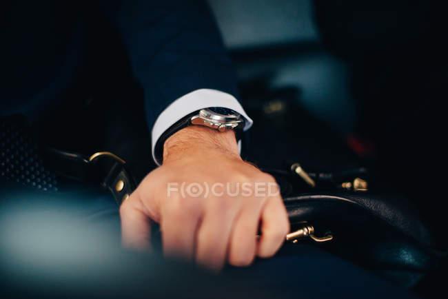 Abgeschnittenes Bild eines gestandenen Geschäftsmannes mit Tasche auf dem Sitz im Taxi — Stockfoto