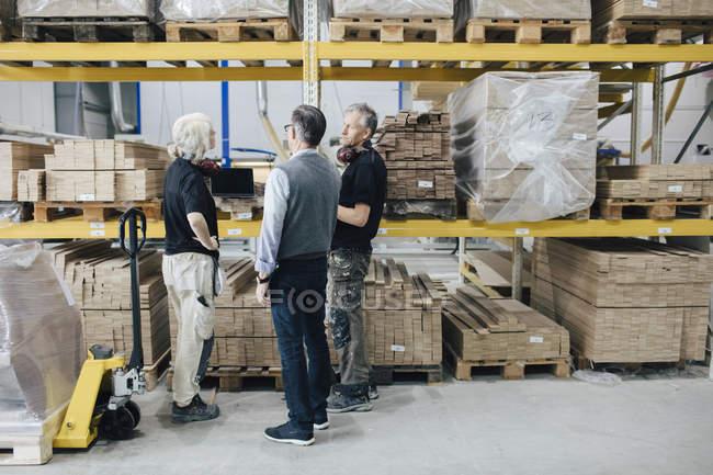 Велика кількість ділових людей, які планують дерев'яні дошки, стоячи в промисловості — стокове фото